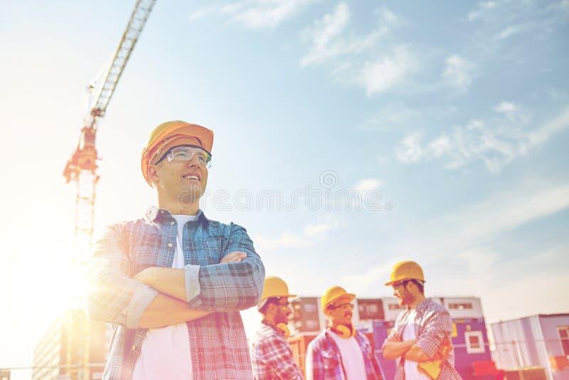 小组在安全帽的微笑的建造者户外 免版税库存图片