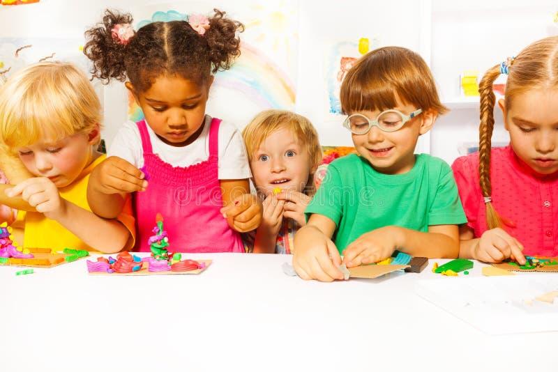小组在幼儿园戏剧的孩子与彩色塑泥 免版税图库摄影