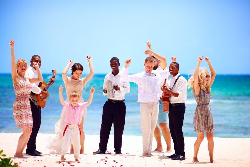 小组在庆祝的愉快的家庭与音乐家的异乎寻常的婚礼,热带海滩的 库存图片