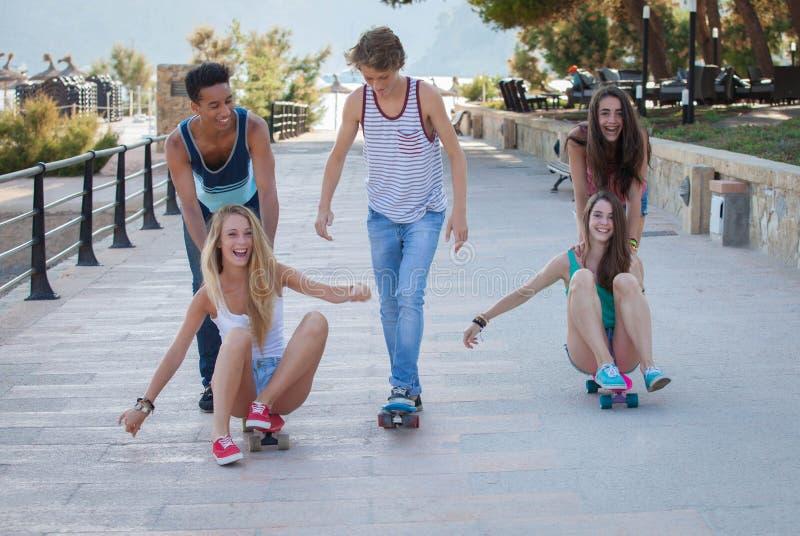 小组在获得的滑板的孩子夏天乐趣 库存图片