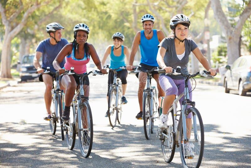 小组在郊区街道上的骑自行车者 免版税库存图片
