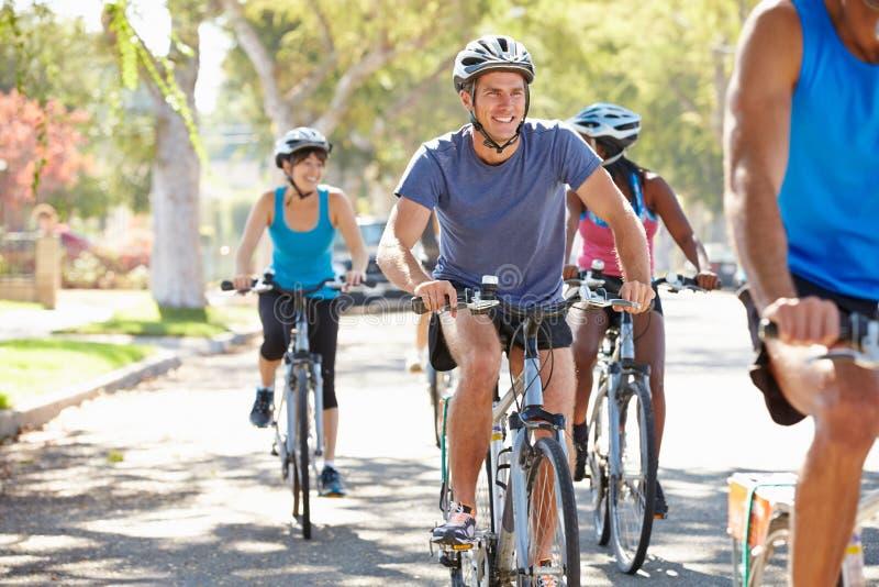 小组在郊区街道上的骑自行车者 免版税库存照片
