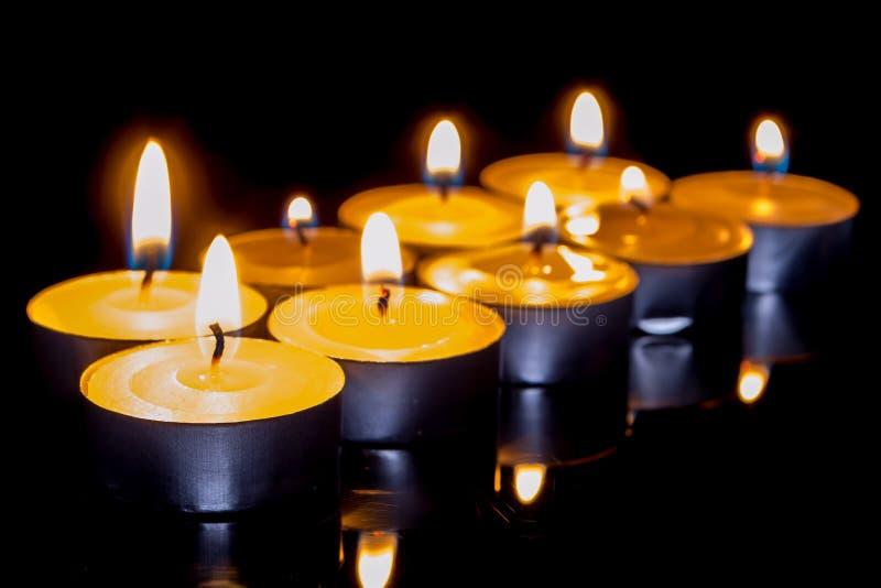 小组在黑背景的灼烧的蜡烛。 免版税图库摄影