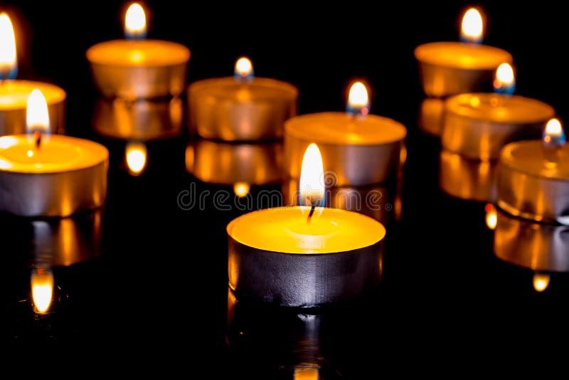 小组在黑背景的灼烧的蜡烛。 免版税库存照片