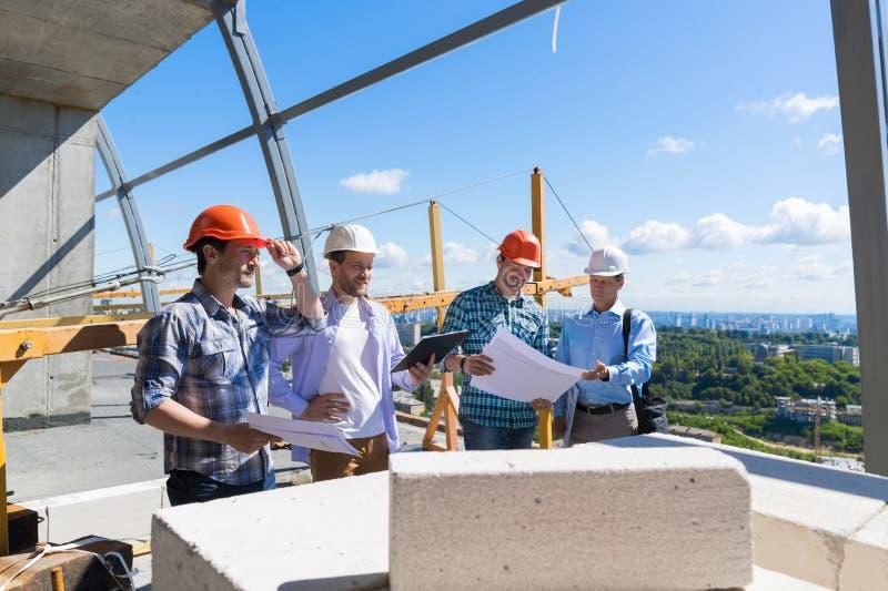 小组在建造场所遇见承包商回顾项目计划的学徒大厦队的建造者  库存图片