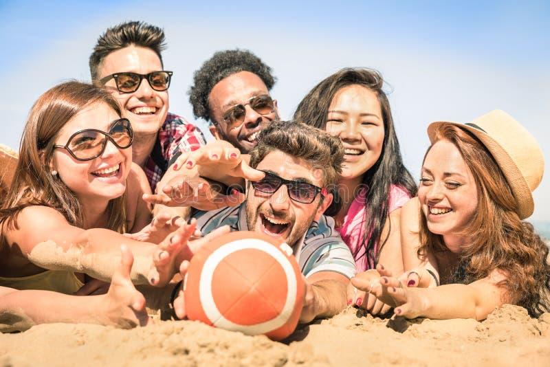 小组多种族愉快的朋友获得乐趣在海滩比赛 图库摄影
