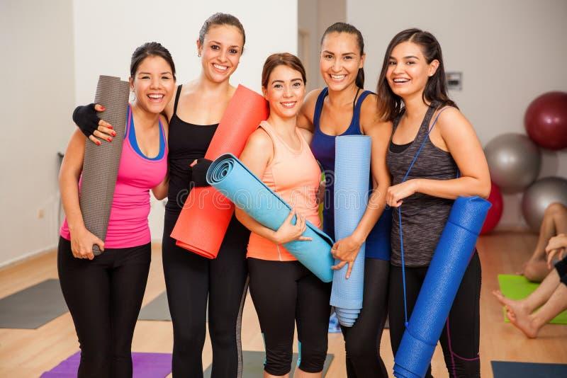 小组女孩在瑜伽演播室 免版税库存图片