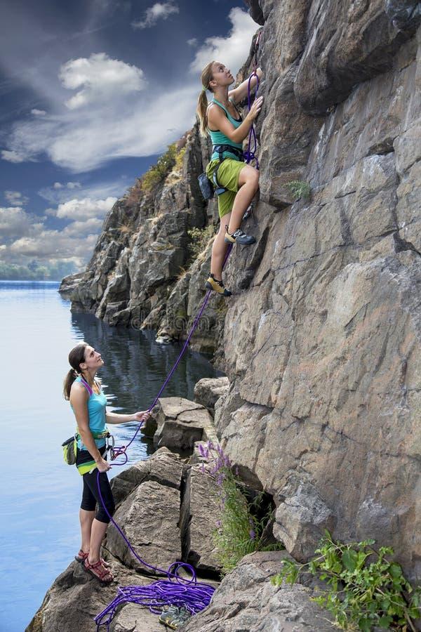 小组女性攀岩运动员做和上升  免版税图库摄影