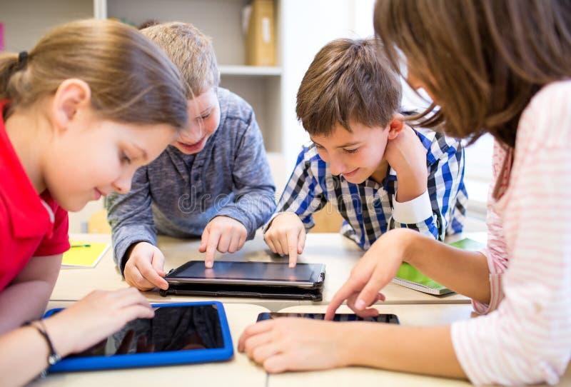 小组学校哄骗与片剂个人计算机在教室 免版税图库摄影