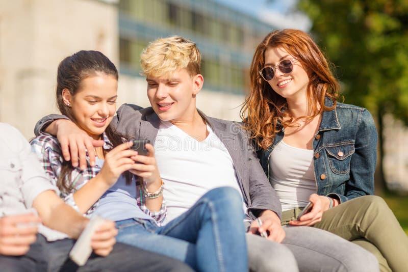 小组学生或少年有智能手机的 免版税库存照片