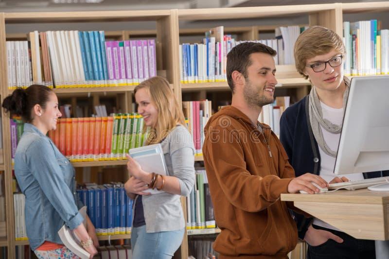 小组学生谈论在图书馆 免版税库存图片