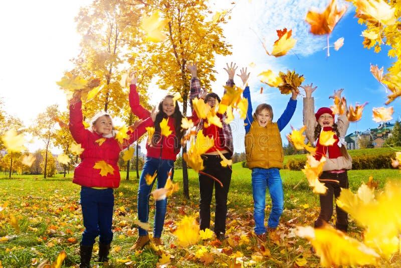 小组孩子投掷秋叶 免版税库存照片