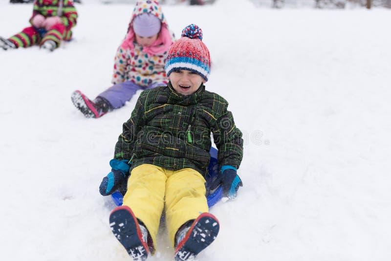 小组孩子有乐趣和戏剧一起在新鲜的雪 免版税库存图片