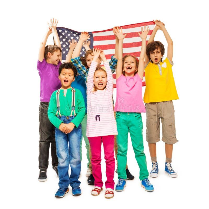 小组孩子被包围在美国国旗下 免版税库存照片