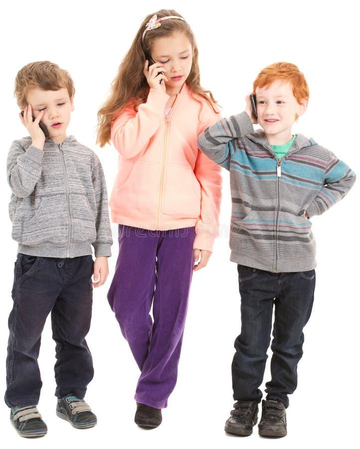 小组孩子谈话在手机。 免版税库存图片