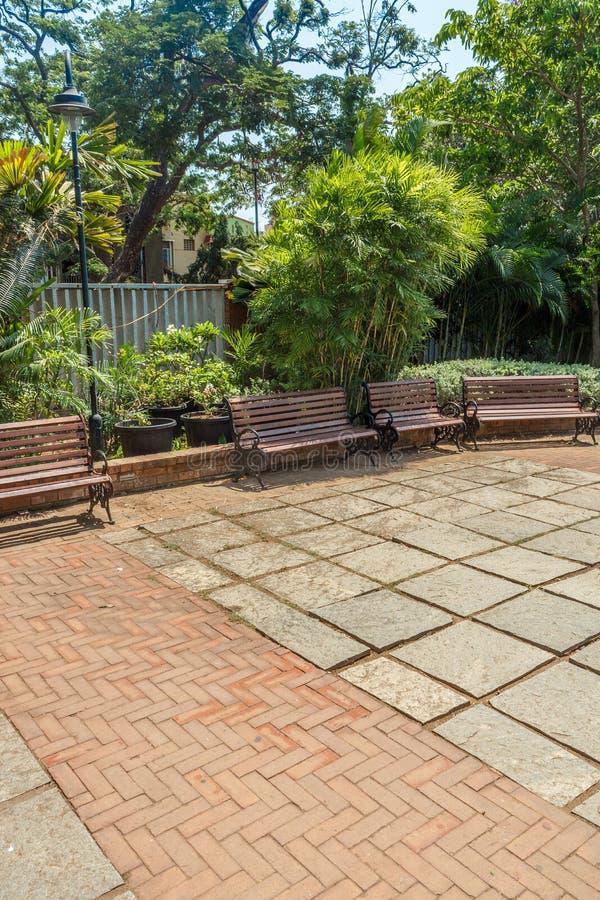 小组宽看法没人住的木位子或椅子在庭院或公园,金奈,印度, 2017年4月1日里安排了 库存照片