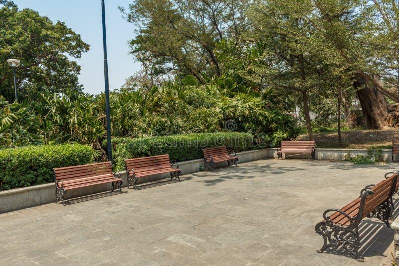 小组宽看法没人住的木位子或椅子在庭院或公园,金奈,印度, 2017年4月1日里安排了 库存图片