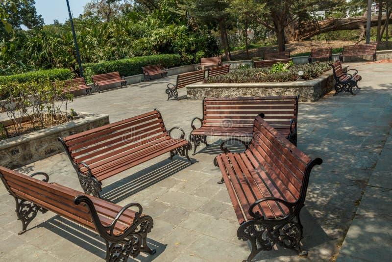 小组宽看法没人住的木位子或椅子在庭院或公园,金奈,印度, 2017年4月1日里安排了 免版税库存图片