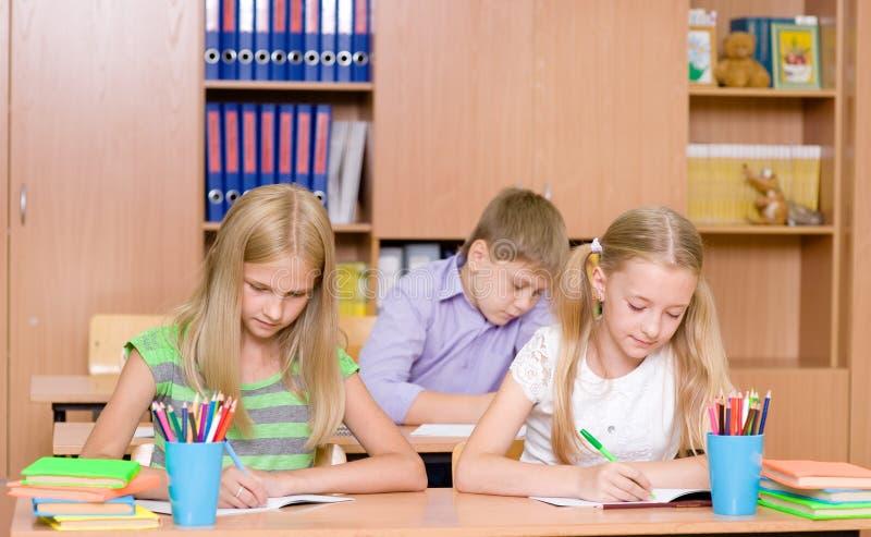 小组小学学生在教室接受考试 免版税库存照片