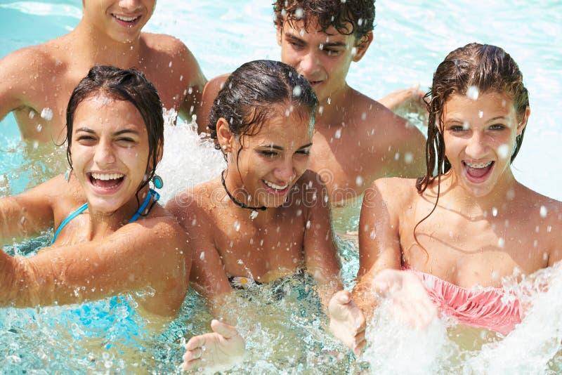 小组少年朋友获得乐趣在游泳池 免版税库存照片