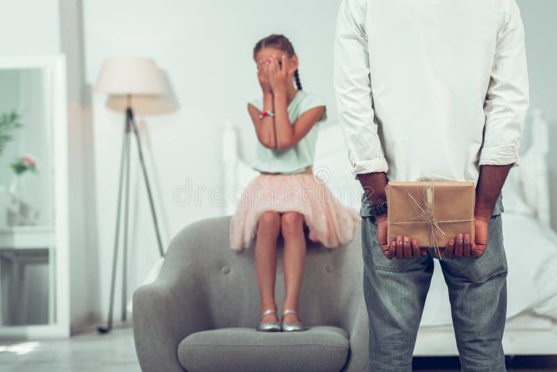 小10年老棕色毛发的逗人喜爱的与棕榈的女孩关闭的眼睛 库存图片