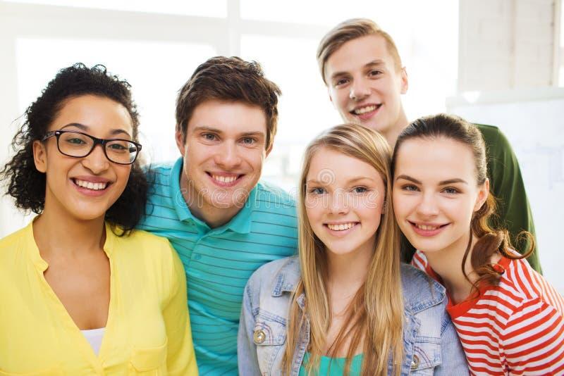 小组微笑的人在学校或家 免版税库存照片