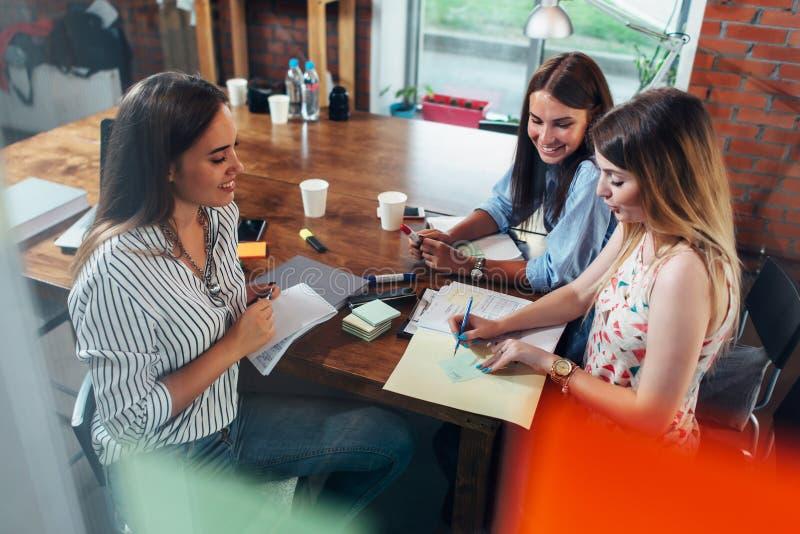小组微笑的创造性的妇女谈论坐在桌附近的项目做笔记在办公室 免版税图库摄影