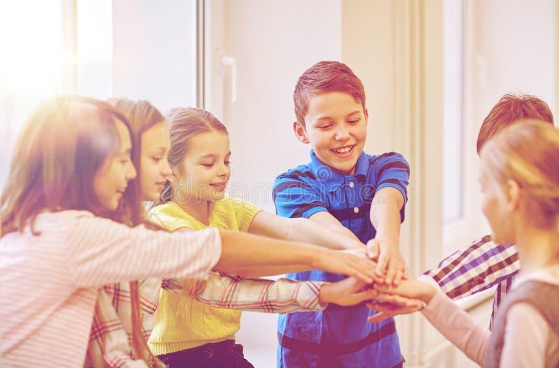 小组微笑的学校哄骗把手放在上面上 免版税库存照片