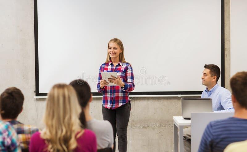 小组微笑的学生和老师在教室 免版税库存图片