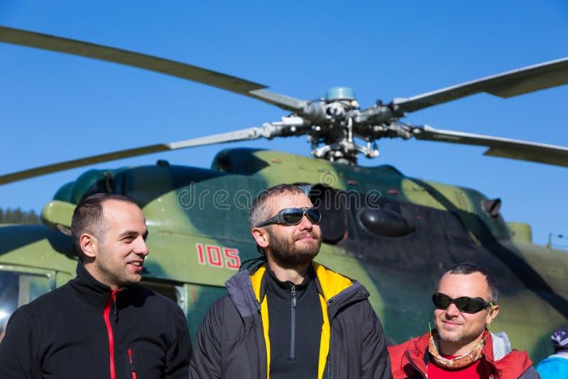 小组微笑的爬山者到达了对异国目的地乘直升机 库存照片