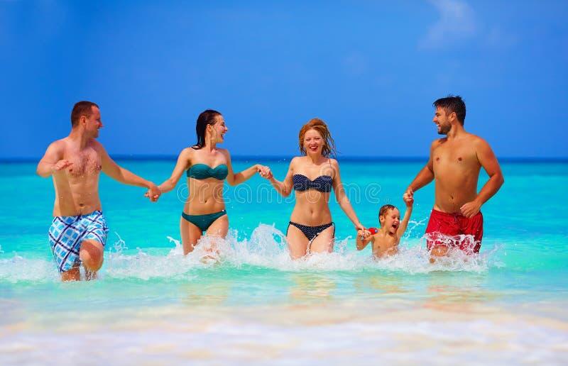 小组快乐的朋友获得乐趣一起在热带海滩 免版税库存照片
