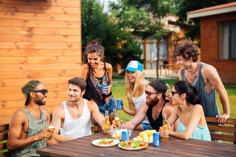 小组年轻快乐的朋友获得乐趣在野餐户外 免版税库存照片
