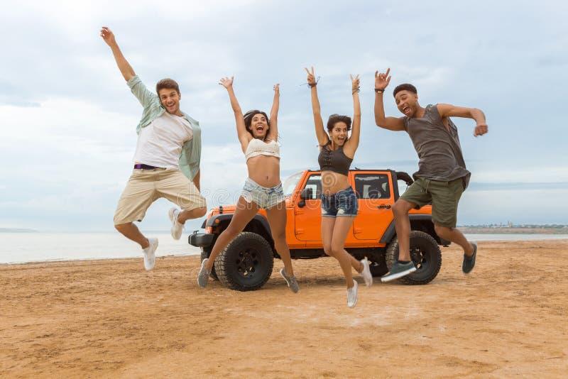 小组愉快不同种族朋友跳跃 免版税库存照片