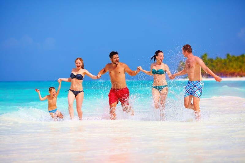 小组愉快的朋友获得乐趣一起在热带海滩 库存图片