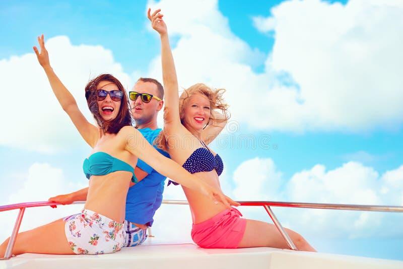 小组愉快的朋友获得在游艇的乐趣,在暑假时 免版税库存图片