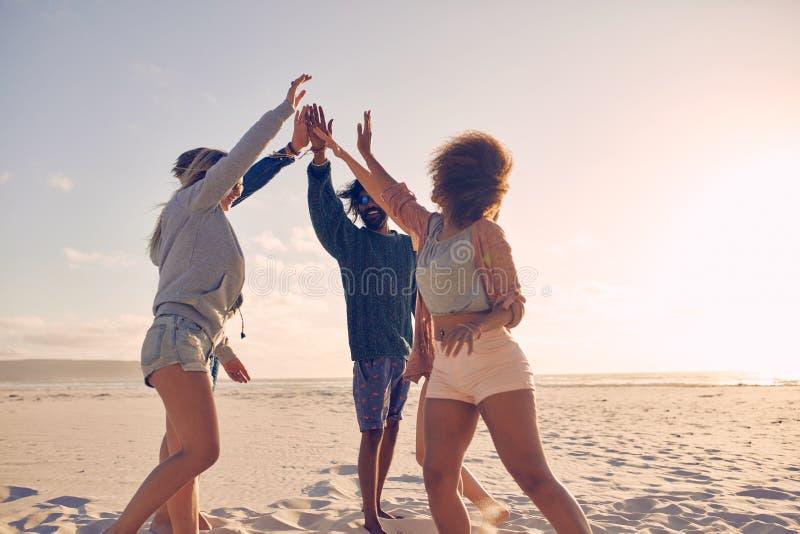 小组愉快的朋友高fiving在海滩 免版税库存图片