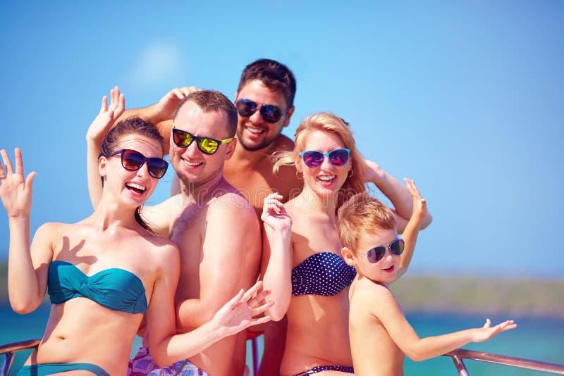 小组愉快的朋友,家庭获得在游艇的乐趣,在暑假时 免版税库存图片