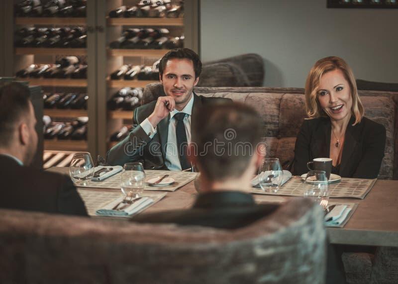 小组成功的商人谈论在工作晚餐期间在餐馆 图库摄影