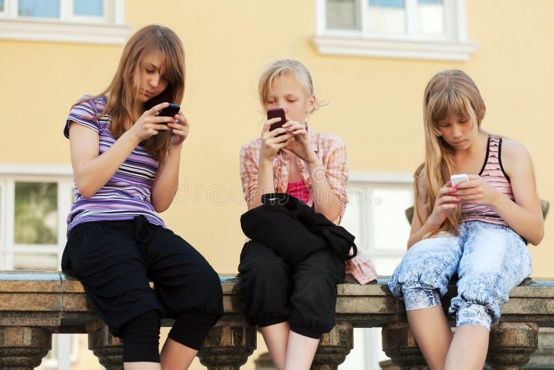 小组拜访电话的学校女孩 免版税库存图片