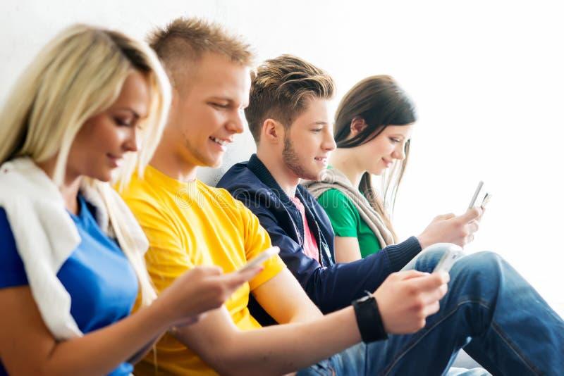 小组断裂的学生 在使用智能手机的男孩的焦点 图库摄影