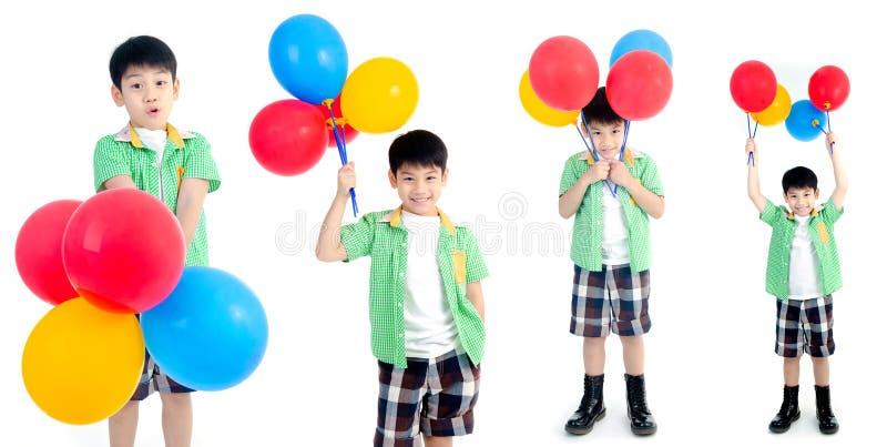 小组有五颜六色的气球的愉快的亚裔逗人喜爱的男孩 免版税库存照片