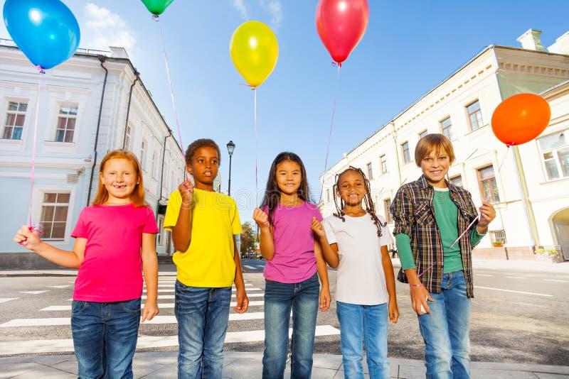 小组有五颜六色的气球的愉快的朋友 免版税图库摄影