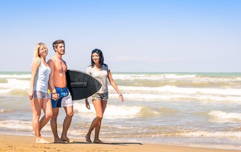 小组有冲浪板的年轻愉快的朋友在海滩 免版税图库摄影