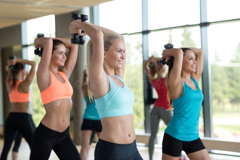 小组有哑铃的妇女在健身房 免版税库存图片