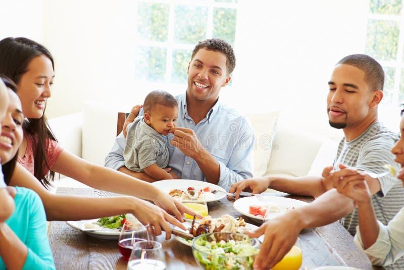 小组有在家享受膳食的婴孩的朋友一起 库存照片