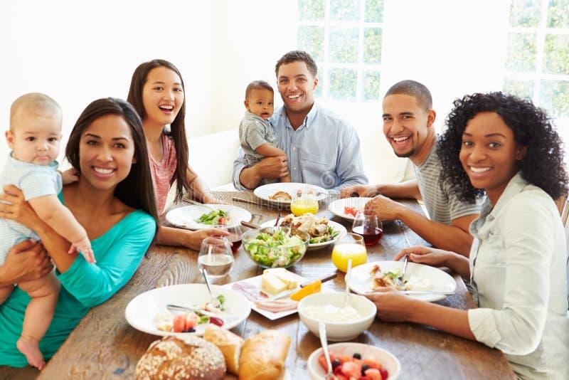 小组有在家享受膳食的婴孩的朋友一起 库存图片