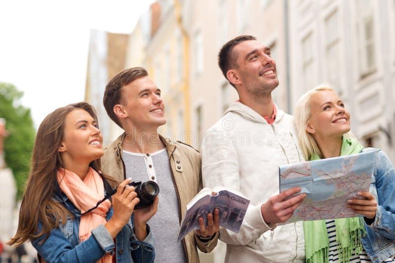 小组有城市指南、地图和照相机的朋友 免版税库存照片