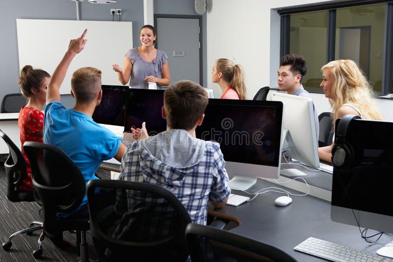 小组有女性家庭教师的学生计算机类的 免版税库存照片