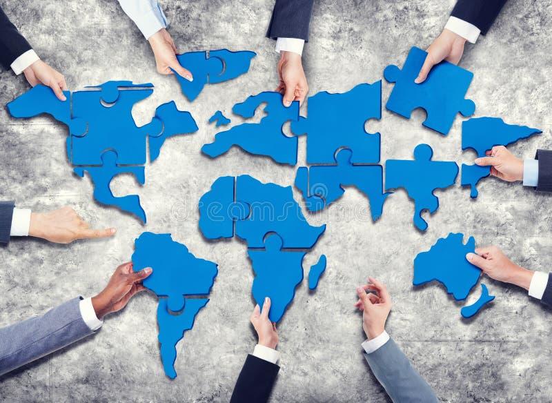 小组有形成在世界地图的七巧板的商人 免版税图库摄影