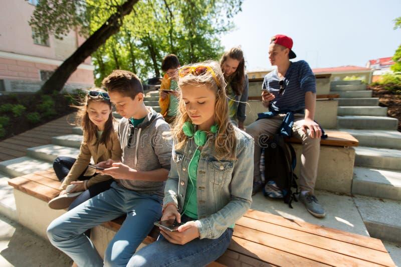 小组有户外智能手机的少年朋友 免版税库存图片